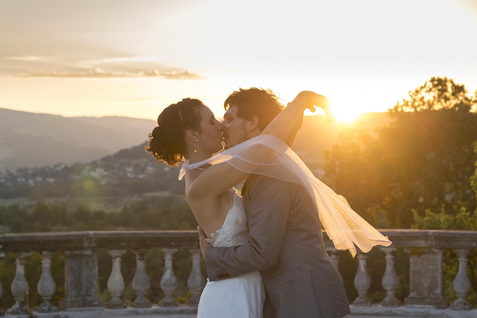 couple de mariés qui s'embrassent au soleil couchant au château de Gourdan en Ardèche