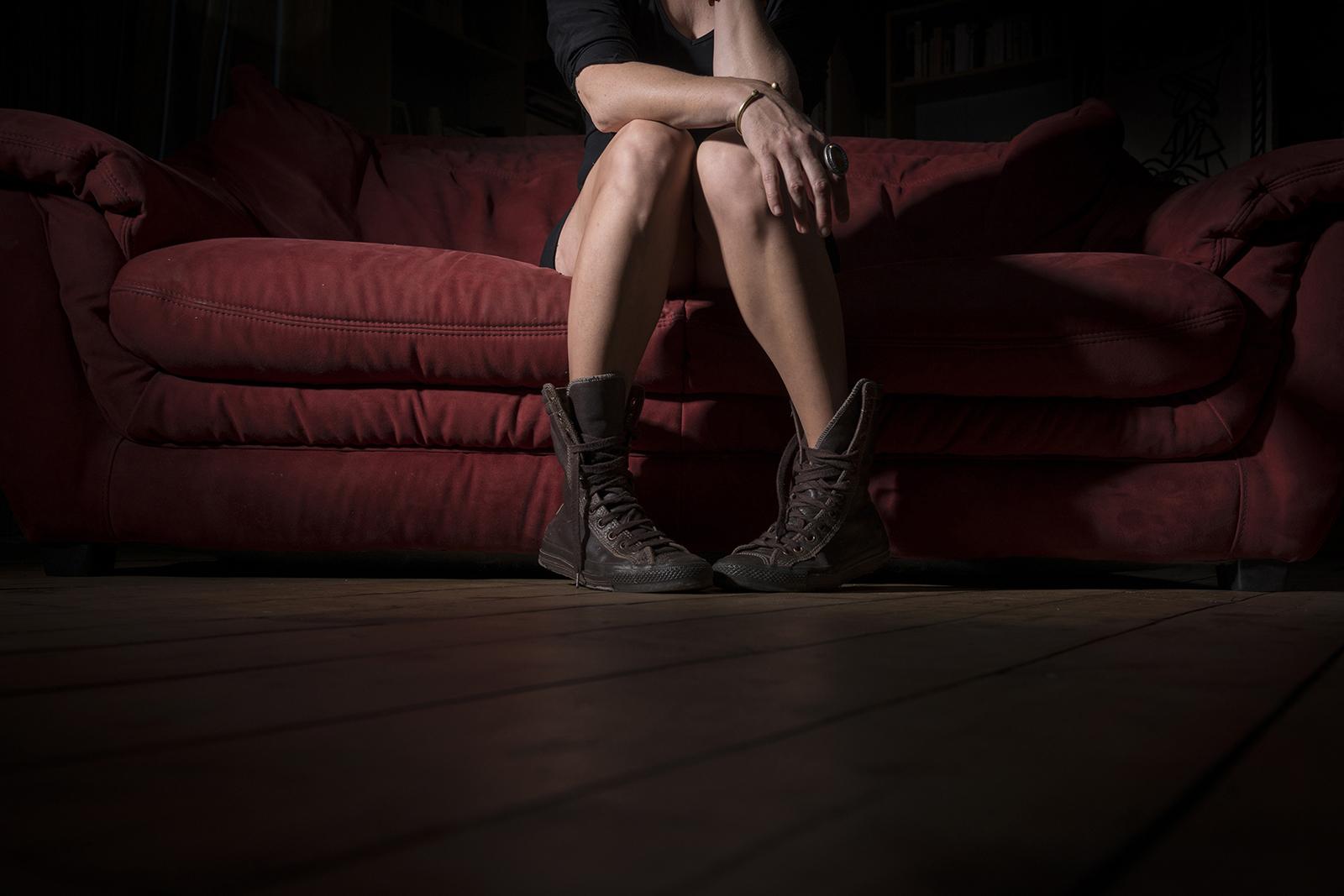 jambes de femme assise sur sofa rouge