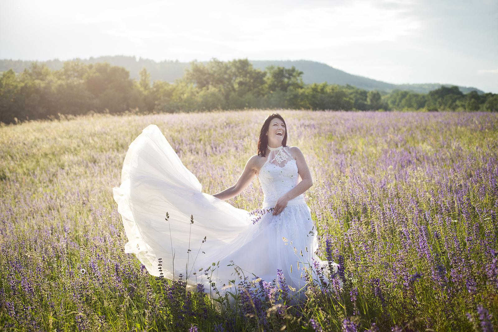 Mariée au coucher du soleil jouant avec sa robe