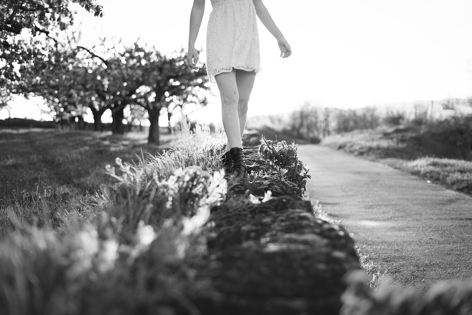 jambes de femme sui marchent sur un mur en pierre