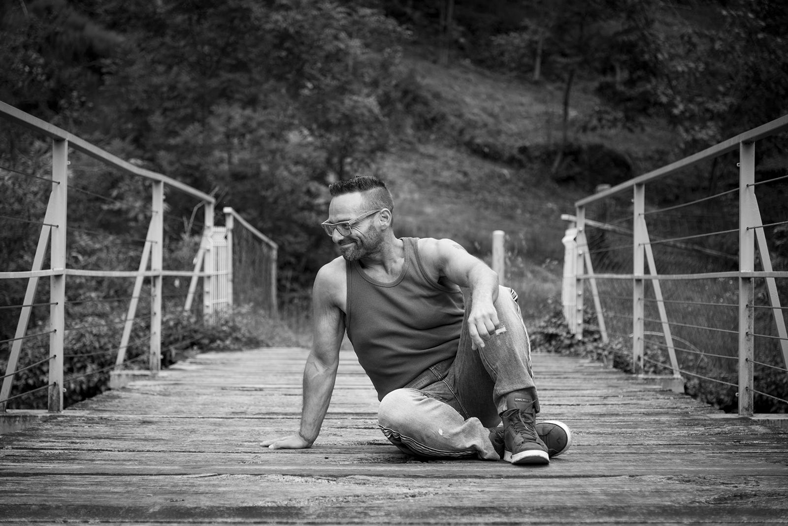 homme assis sur une passerelle noir et blanc
