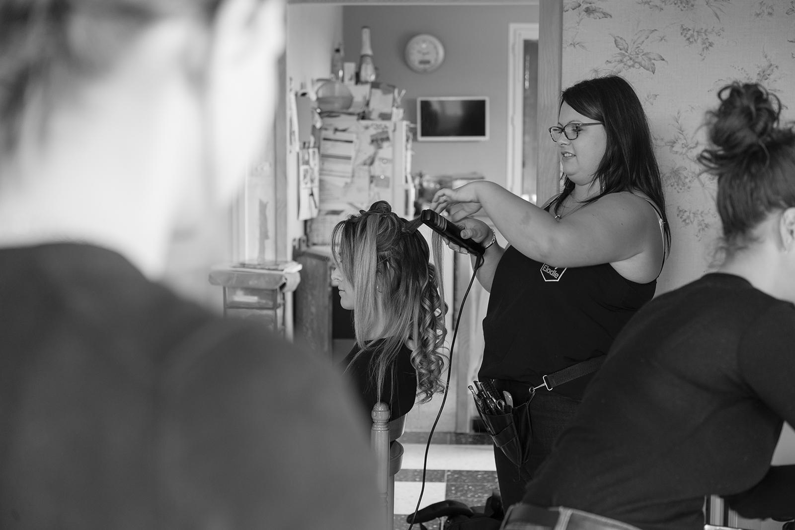 photo noir et blanc d'une coiffeuse au travail