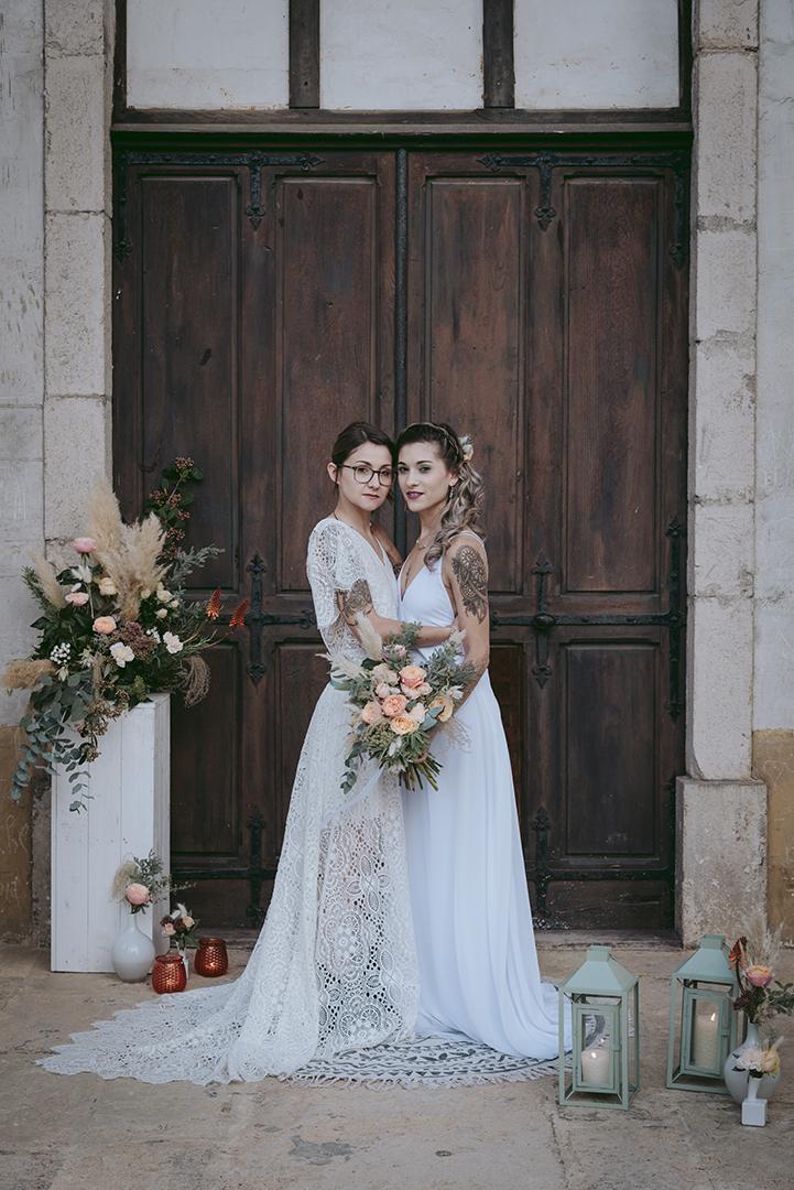 Deux mariées devant une vieille porte en bois et déco pêche et menthe