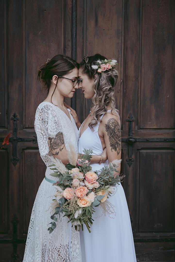 Deux mariées de profil devant une vieille porte en bois