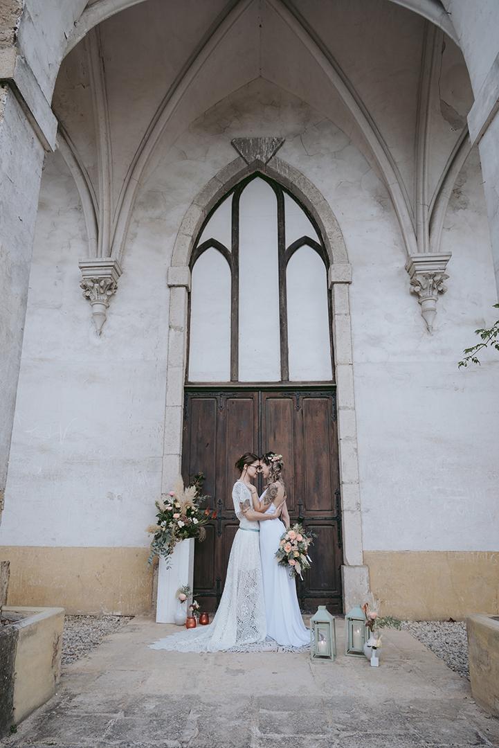 Deux mariées devant une vieille porte en bois d'une chapelle gothique