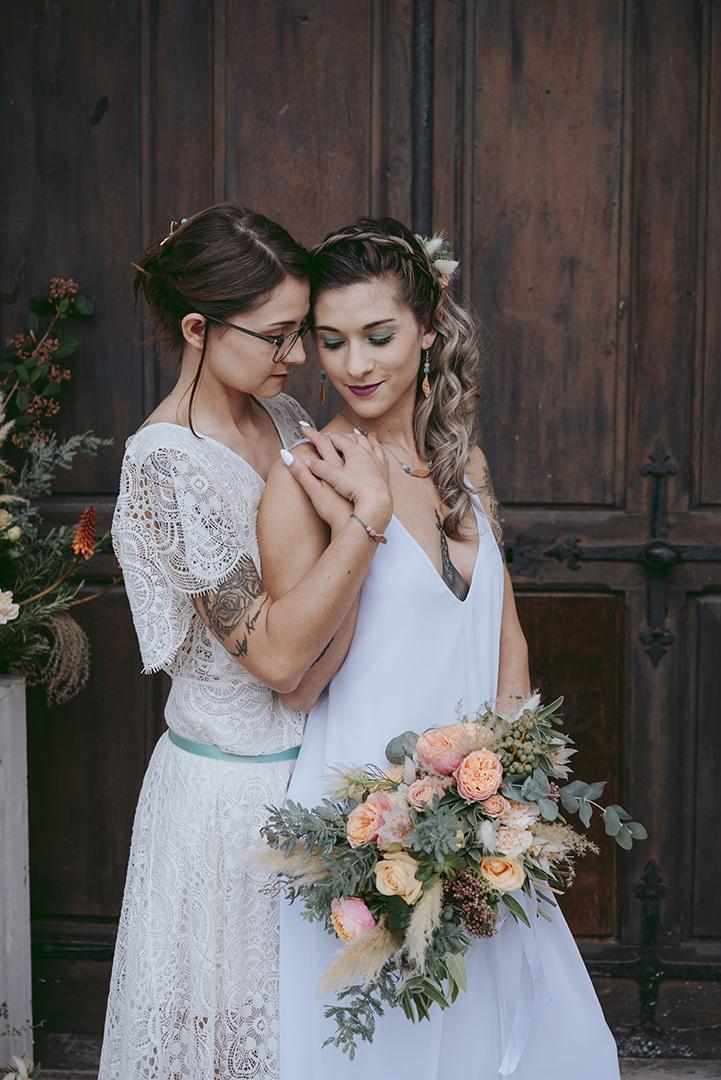 Deux mariées devant une vieille porte en bois