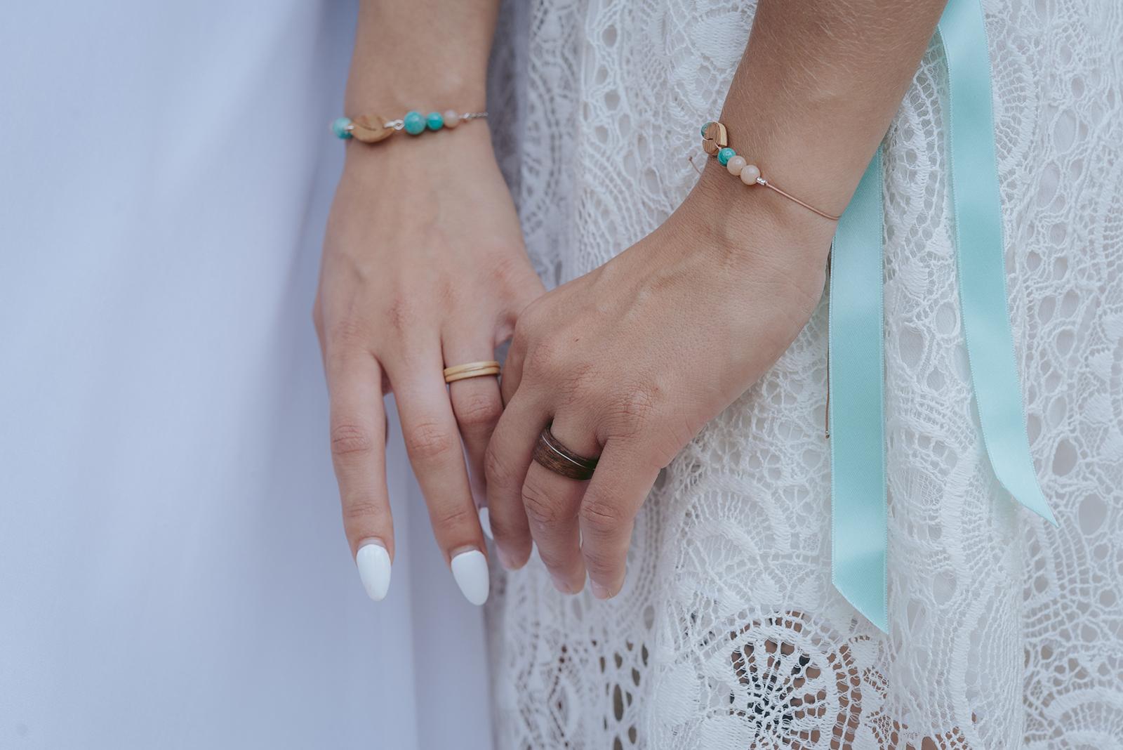 deux mains de femmes avec alliance et bois et bracelets en pierre naturelle