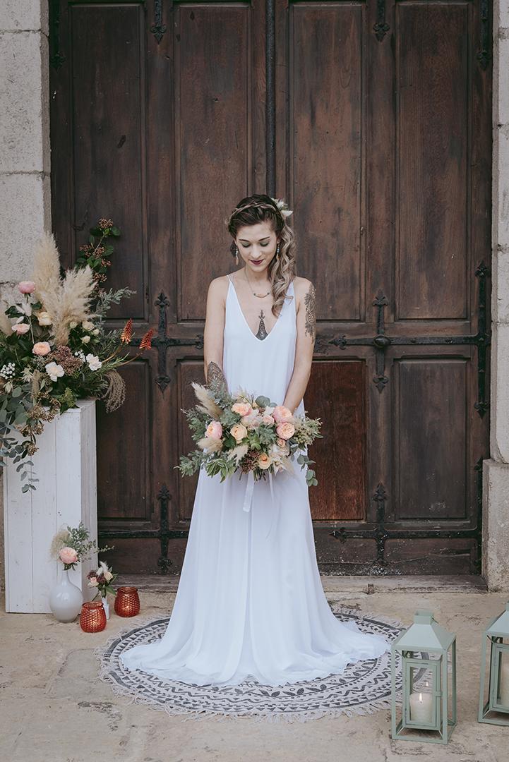 Mariée devant une vieille porte en bois