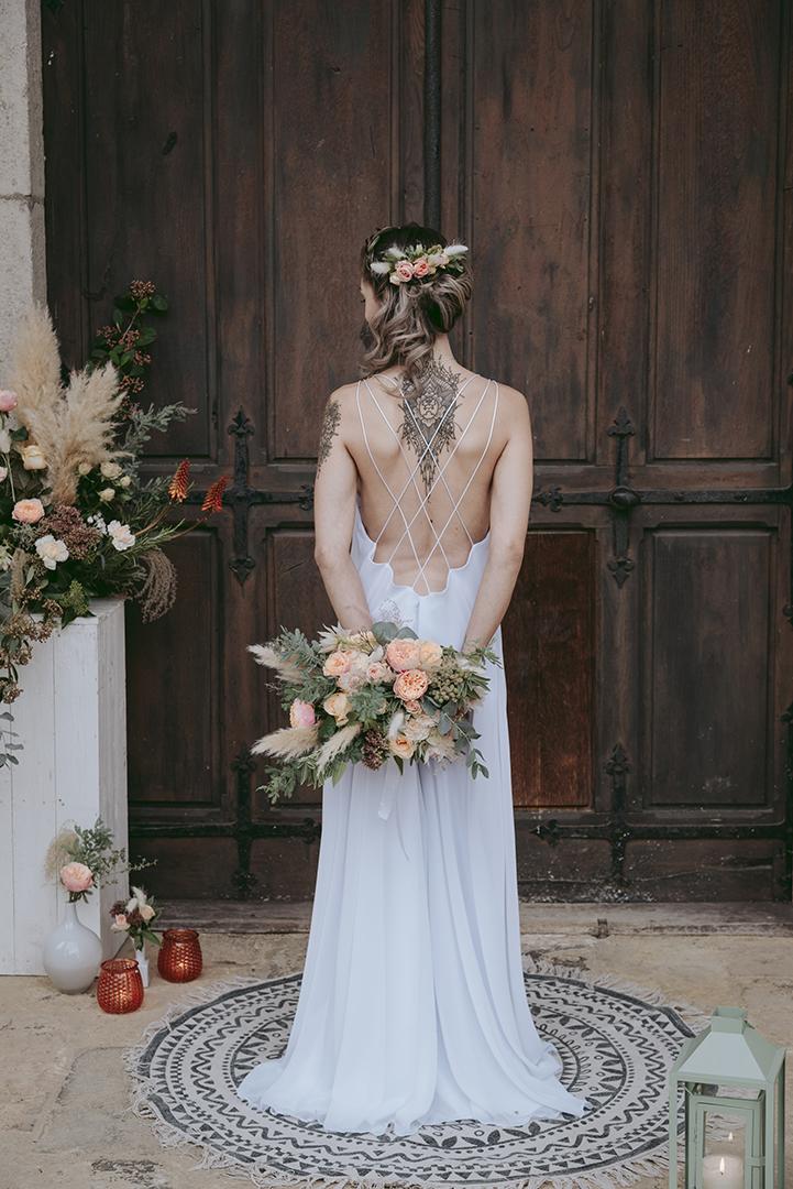 Mariée de dos devant une vieille porte en bois