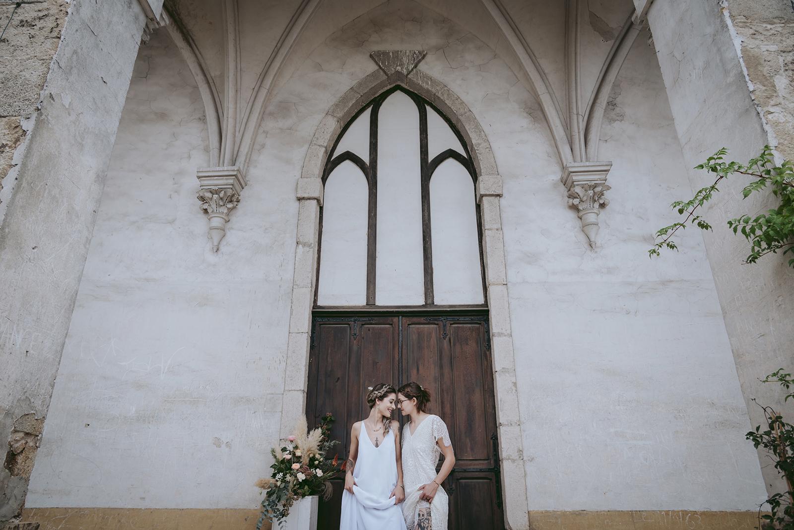 deux mariées devant le parvis d'une chapelle gothique