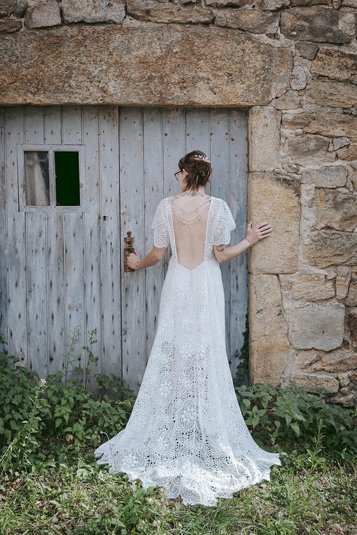 mariée de dos décolleté robe devant vieille porte
