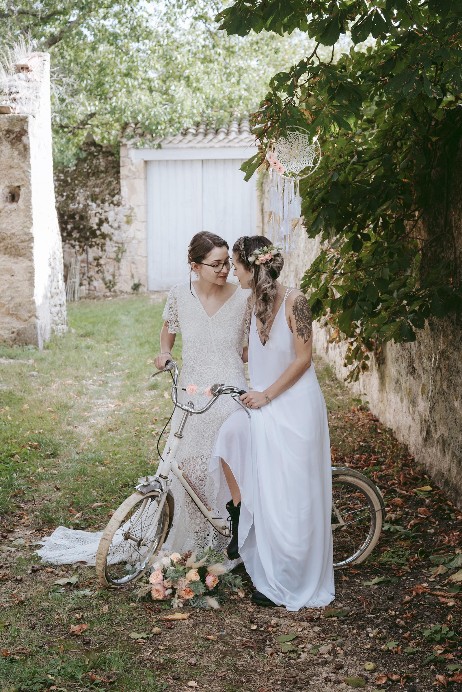 deux mariées sur un vélo dans un chemin avec une vieille porte