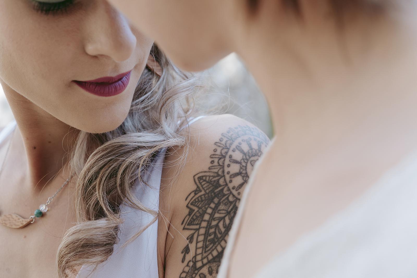 gros plan cheveux bouclés et épaule tatouée