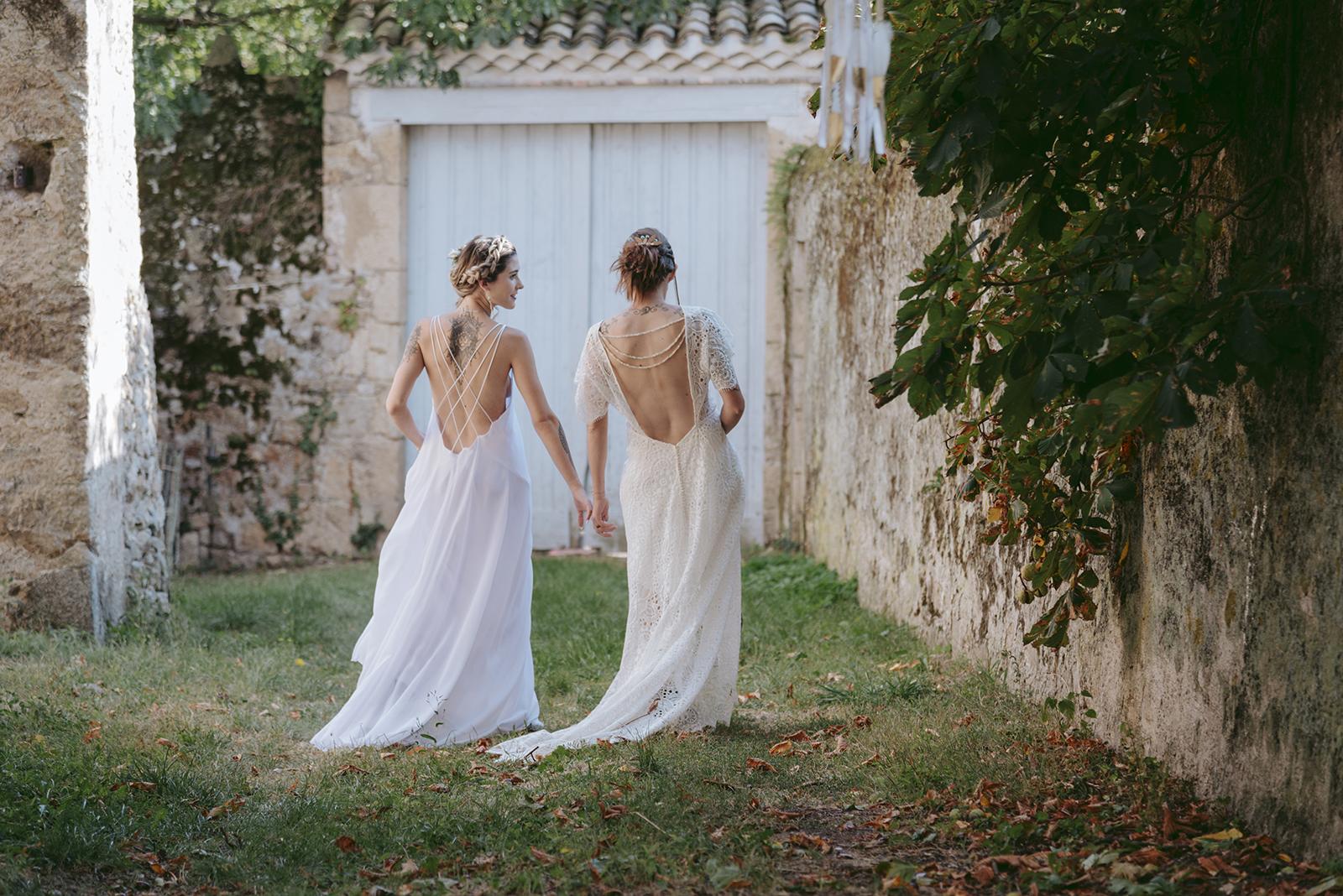 deus femmes en robe de mariée qui marchent de dos