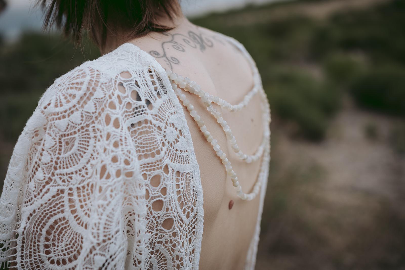 photo de detail dos robe de mariée dentelle et perles