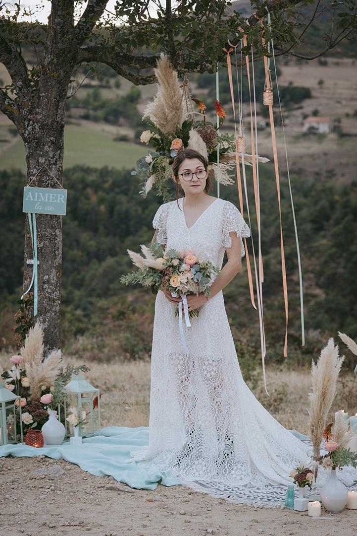 mariée dans une robe à dentelle avec déco pêche et menthe