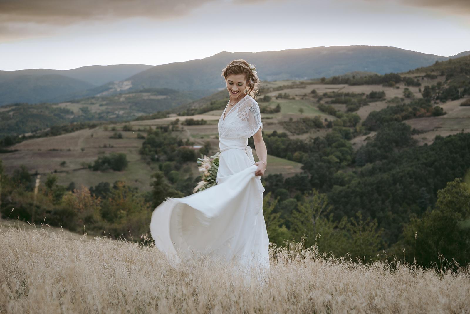 mariée qui joue avec sa robe au crepuscule
