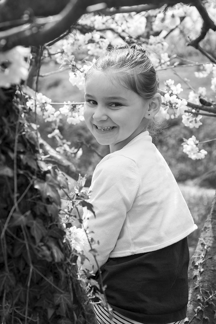 petite fille dans cerisier en fleur en noir et blanc