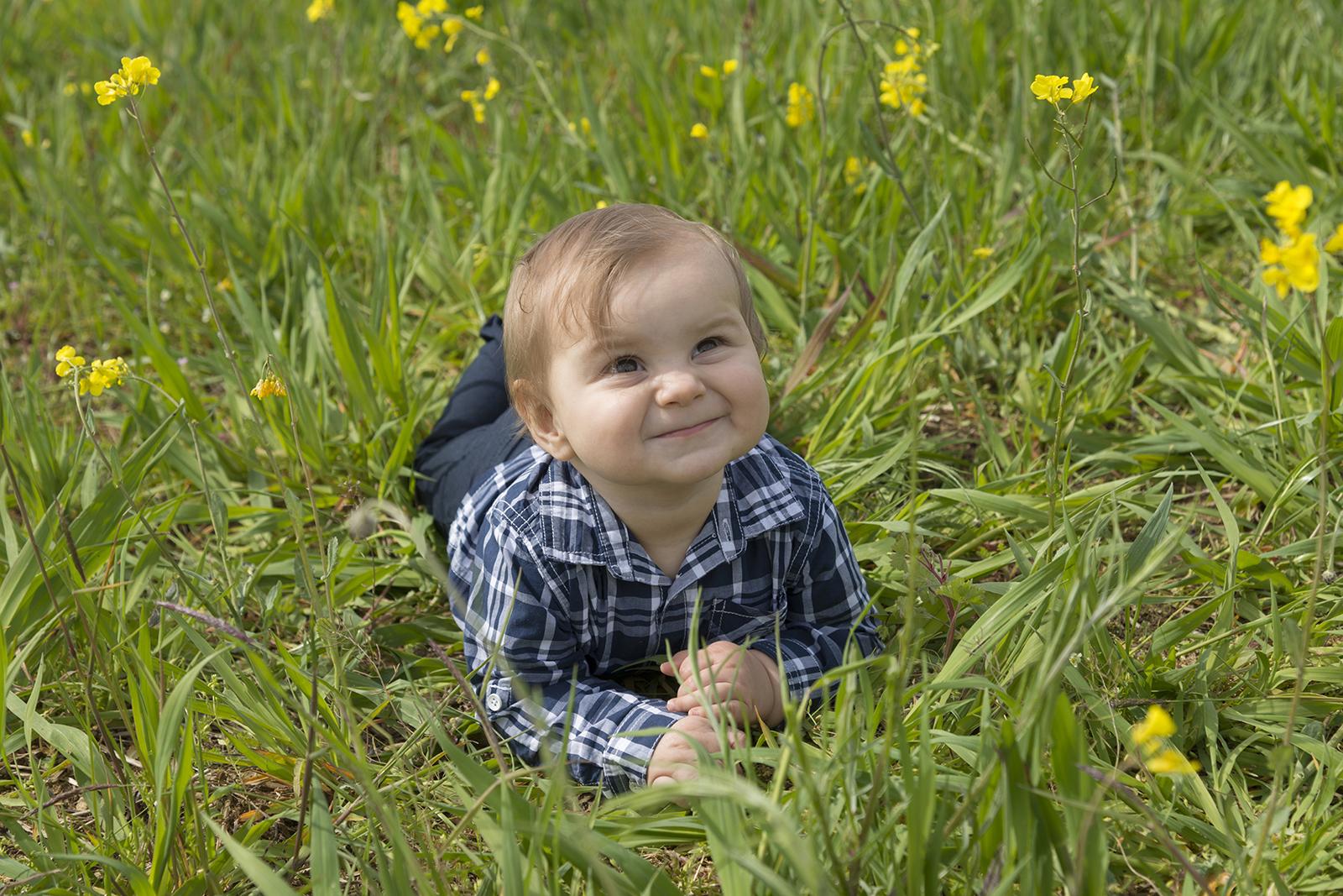 petit garçon dans l'herbe à plat ventre