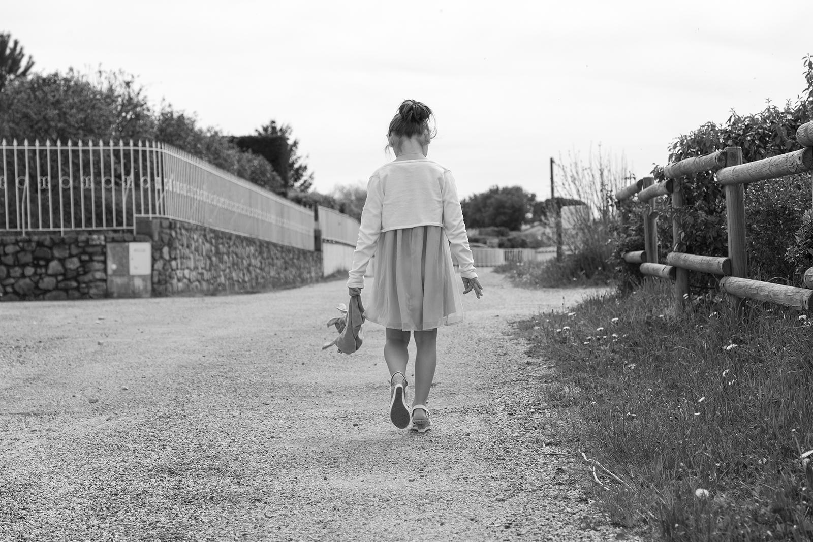photo en noir et blanc d'une petite fille qui marche de dos