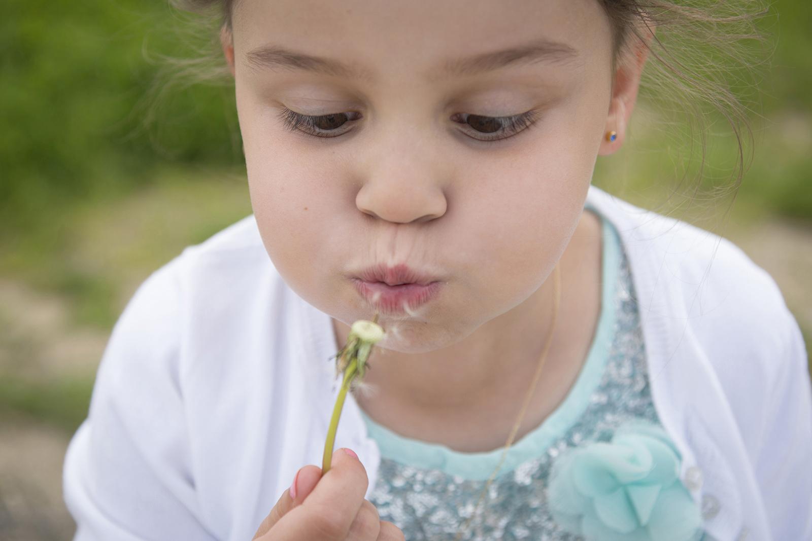 photo petite fille qui souffle un pissenlit