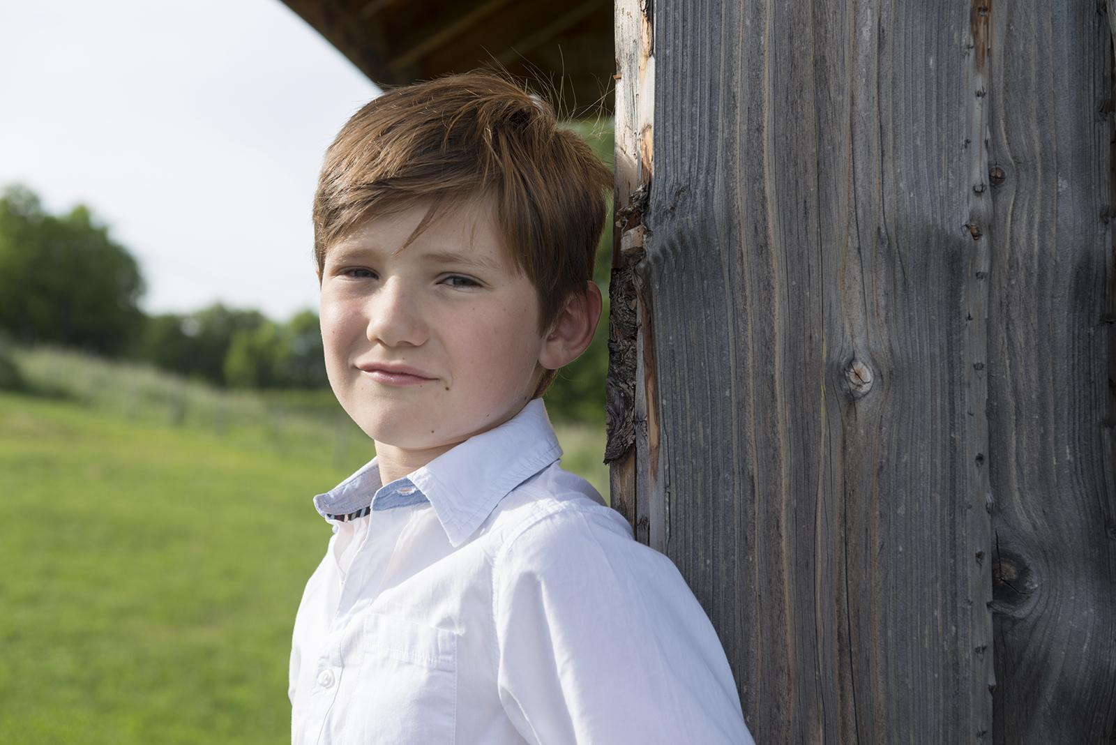jeune garçon adossé à la cabane