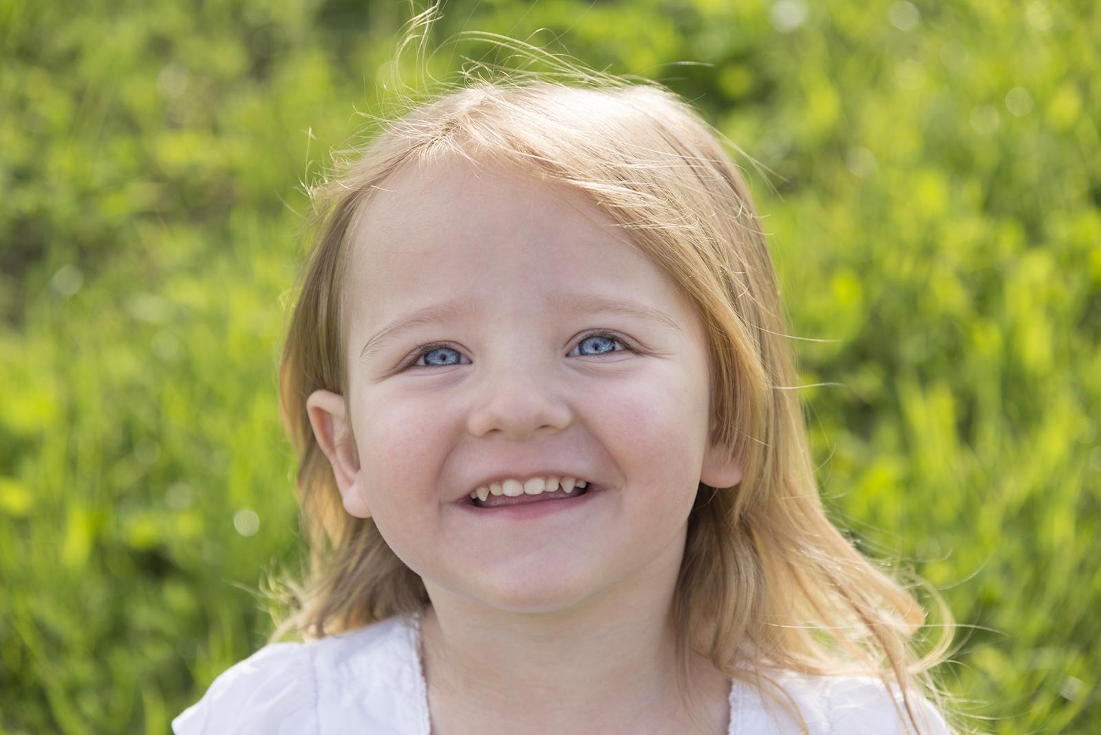 petite fille aux yeux bleus dans l'herbe