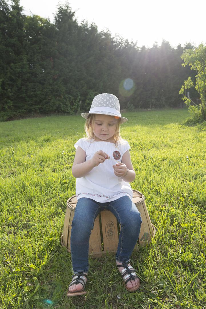 petite fille au chapeau assis sur un mussi