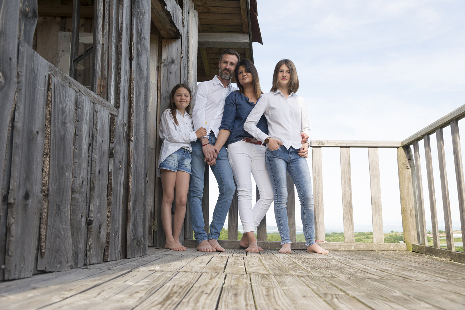 famille sur la terrasse d'une cabane en bois