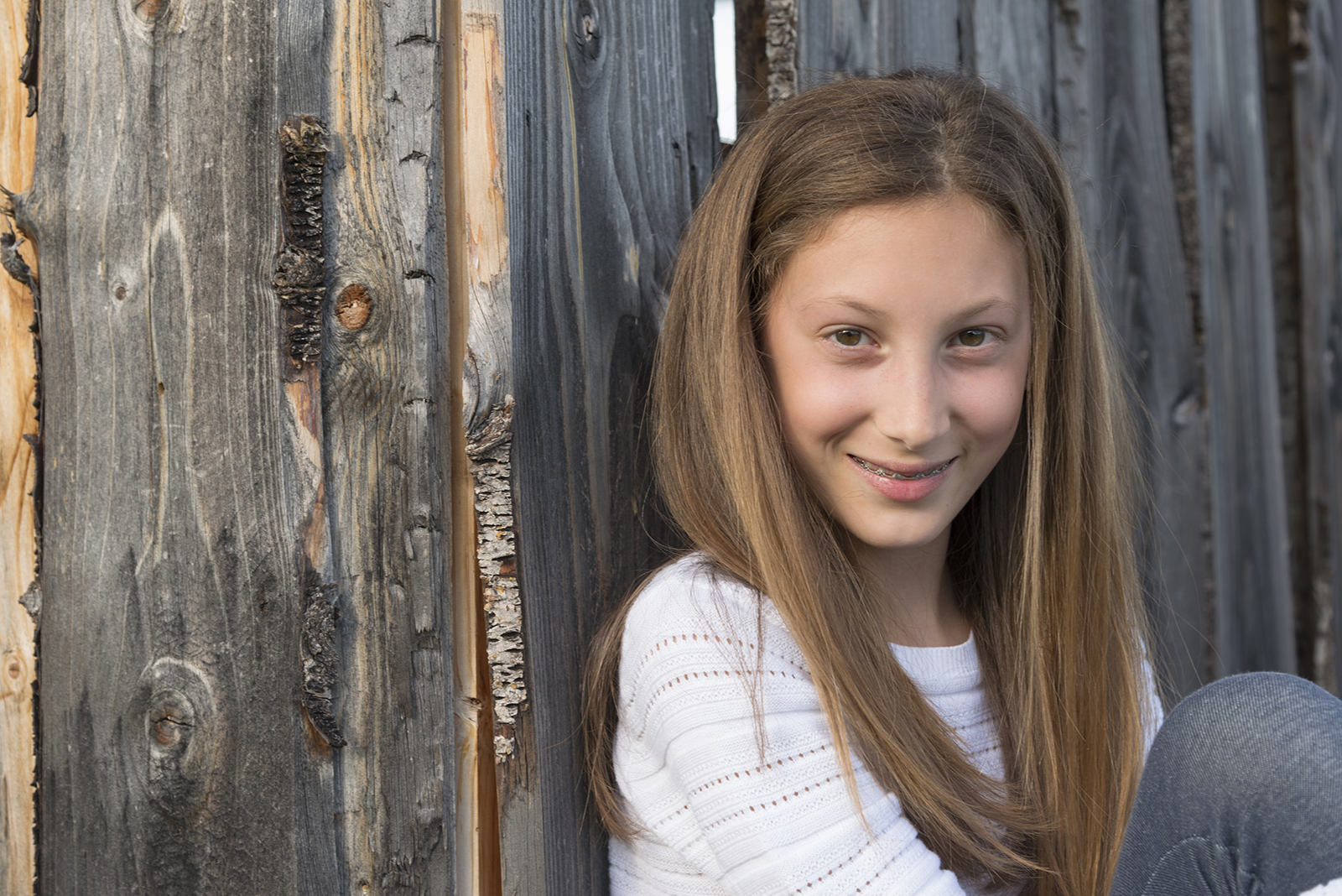 jeune fille adossée à un mu en bois