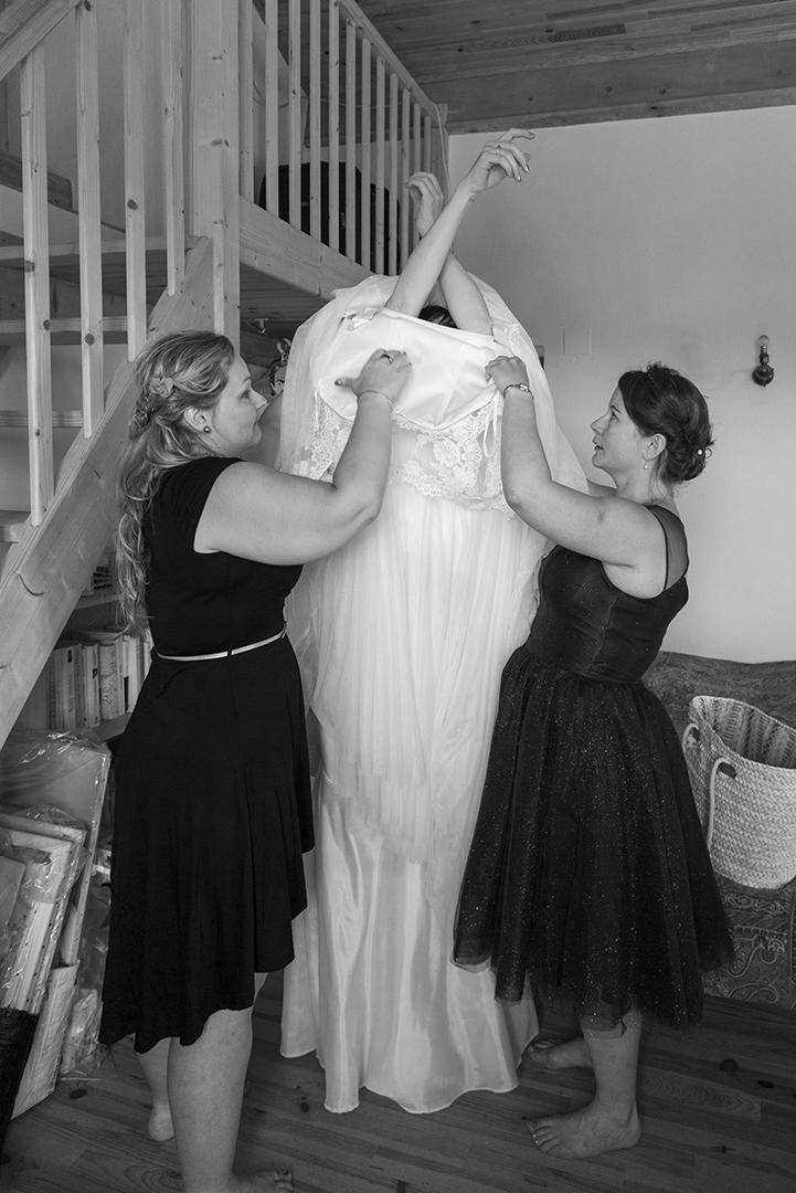 préparatif mariée qui enfile sa robe