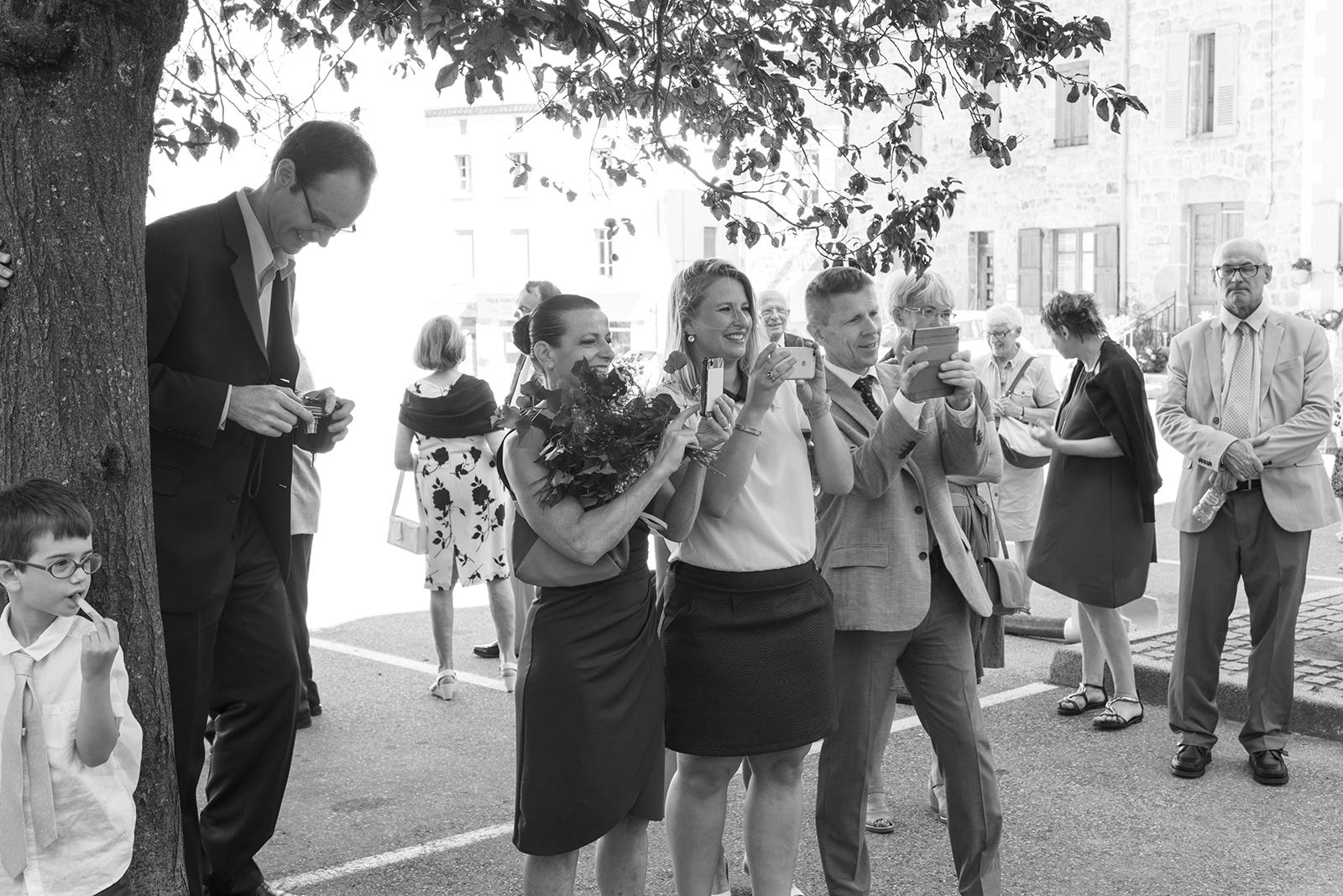 invités mariage noir et blanc qui photographient les mariés