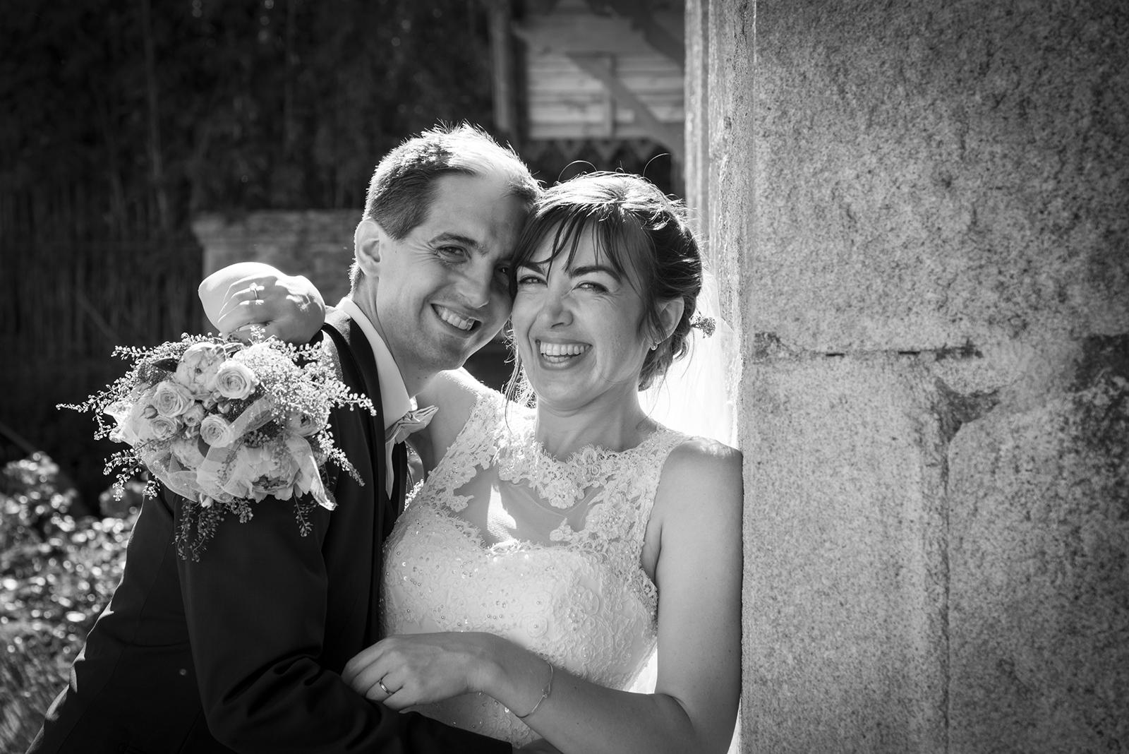 couple mariés qui rient en noir et blanc à contre jour