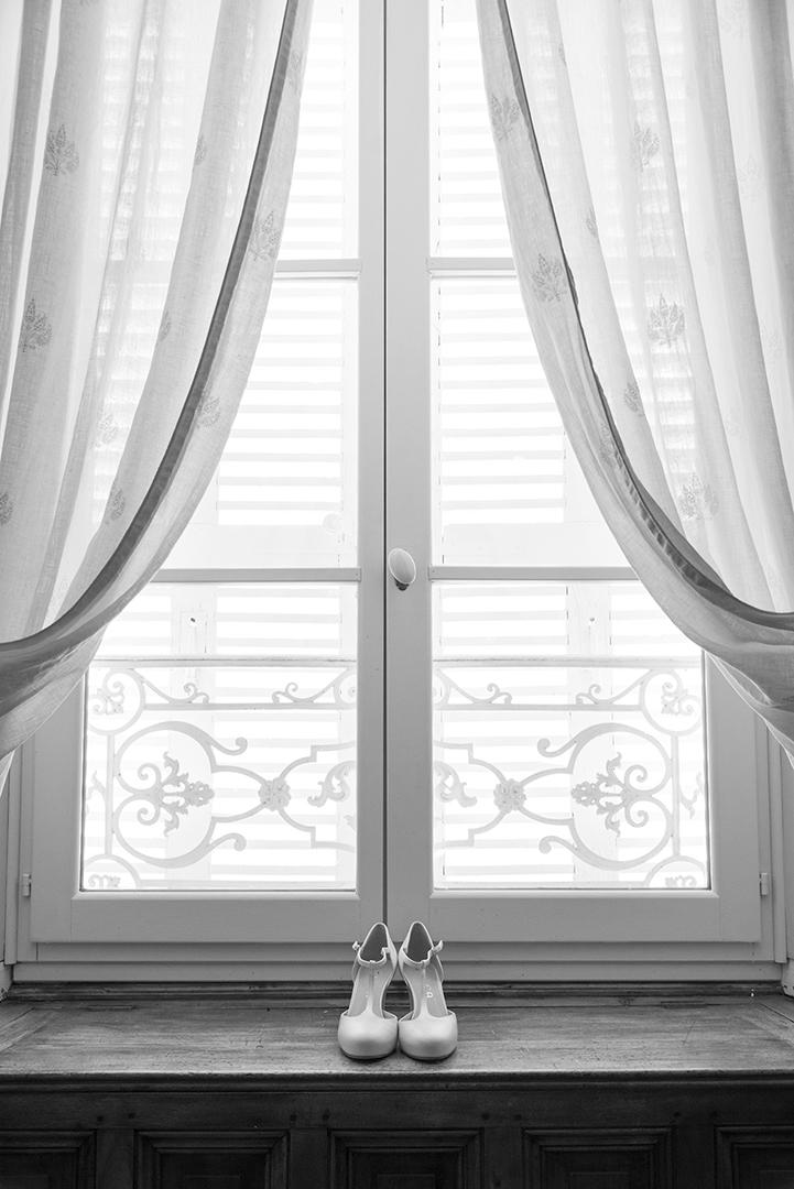 Photo noir et blanc chaussures de mariée sur le rebard d'une fenêtre au château des Gaudras à Roiffieux
