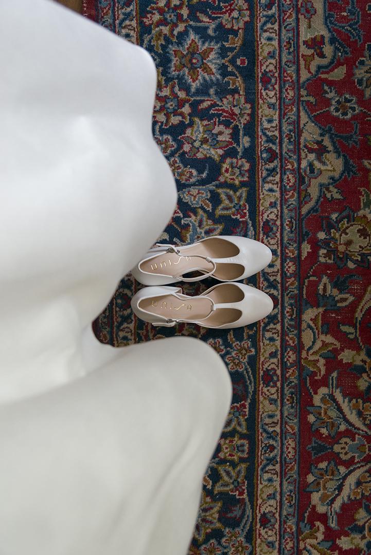 chaussure de mariée sur tapis persan et bas de la robe de mariée