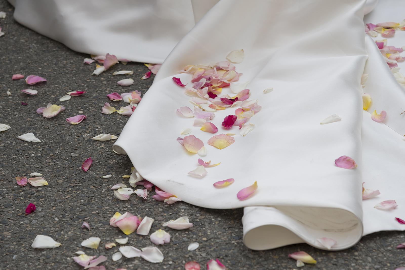 pétale de rose sur robe de mariée à la sortie d'église