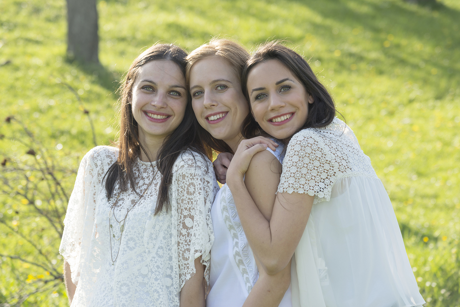 Portrait de trois jeunes femmes vetues de blanc en exterieur