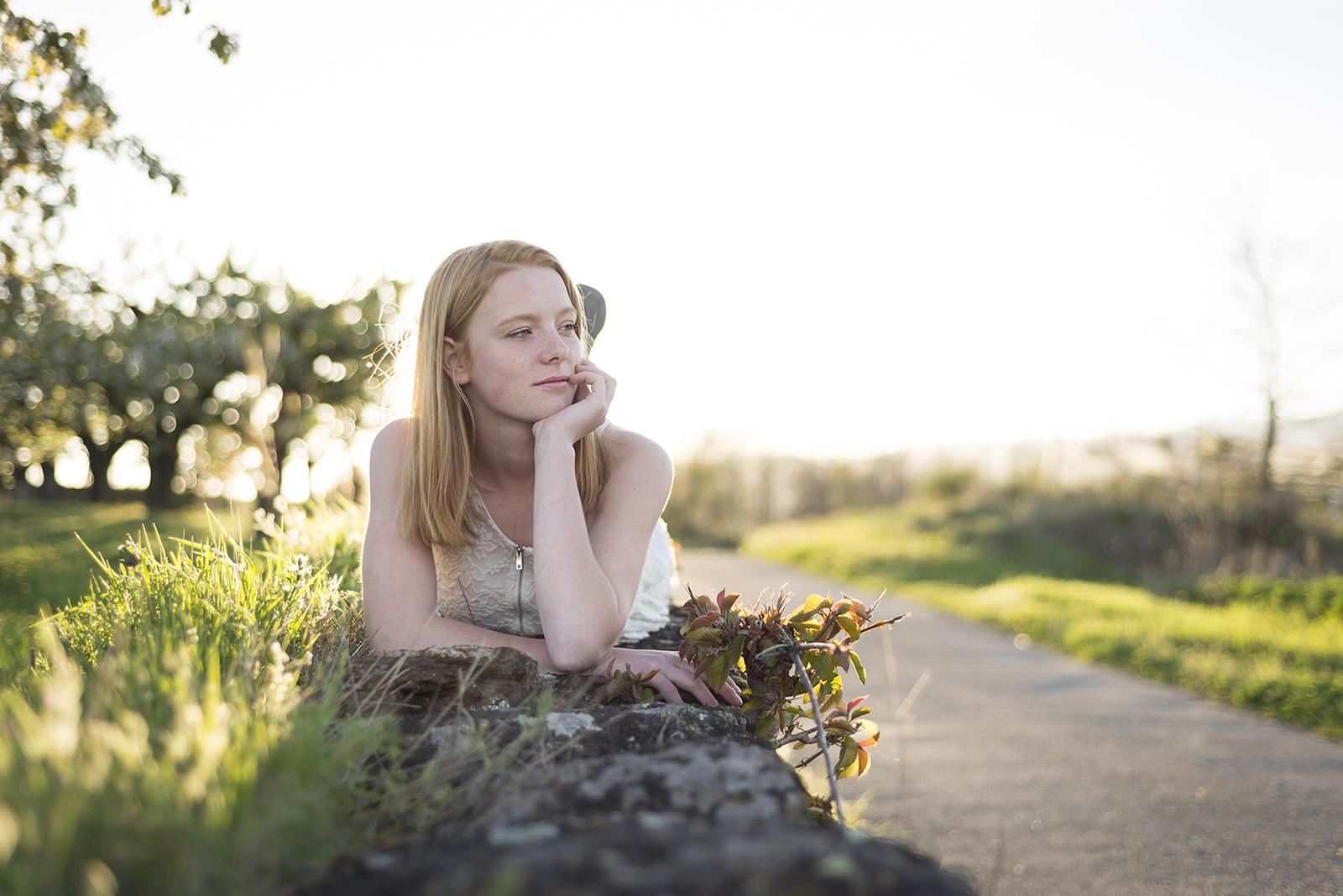 jeune fille sur un mur au coucher du soleil