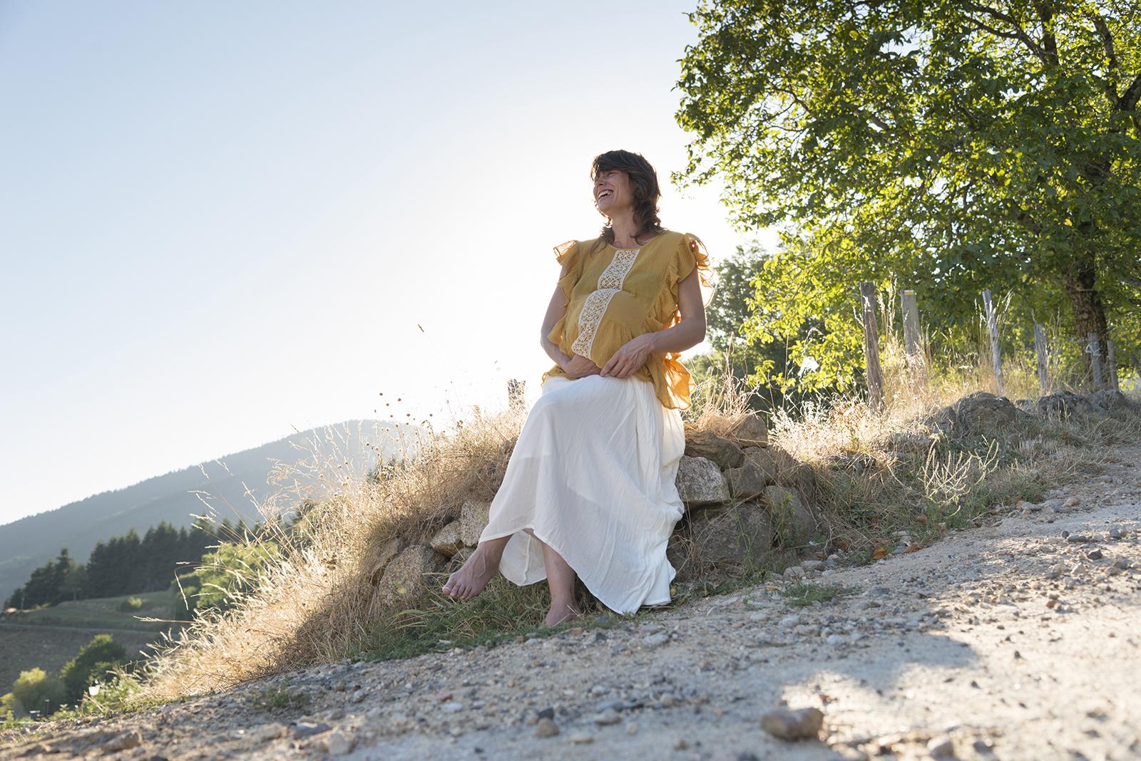 femme enceinte au coucher du soleil assise sur un mur