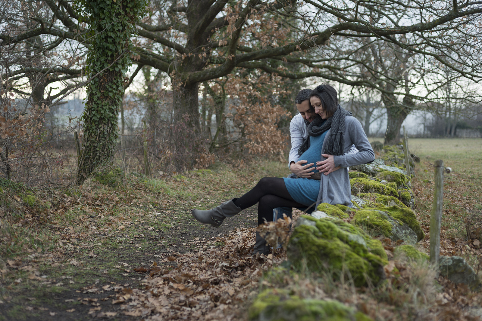 couple femme enceinte assis sur un muret en hiver