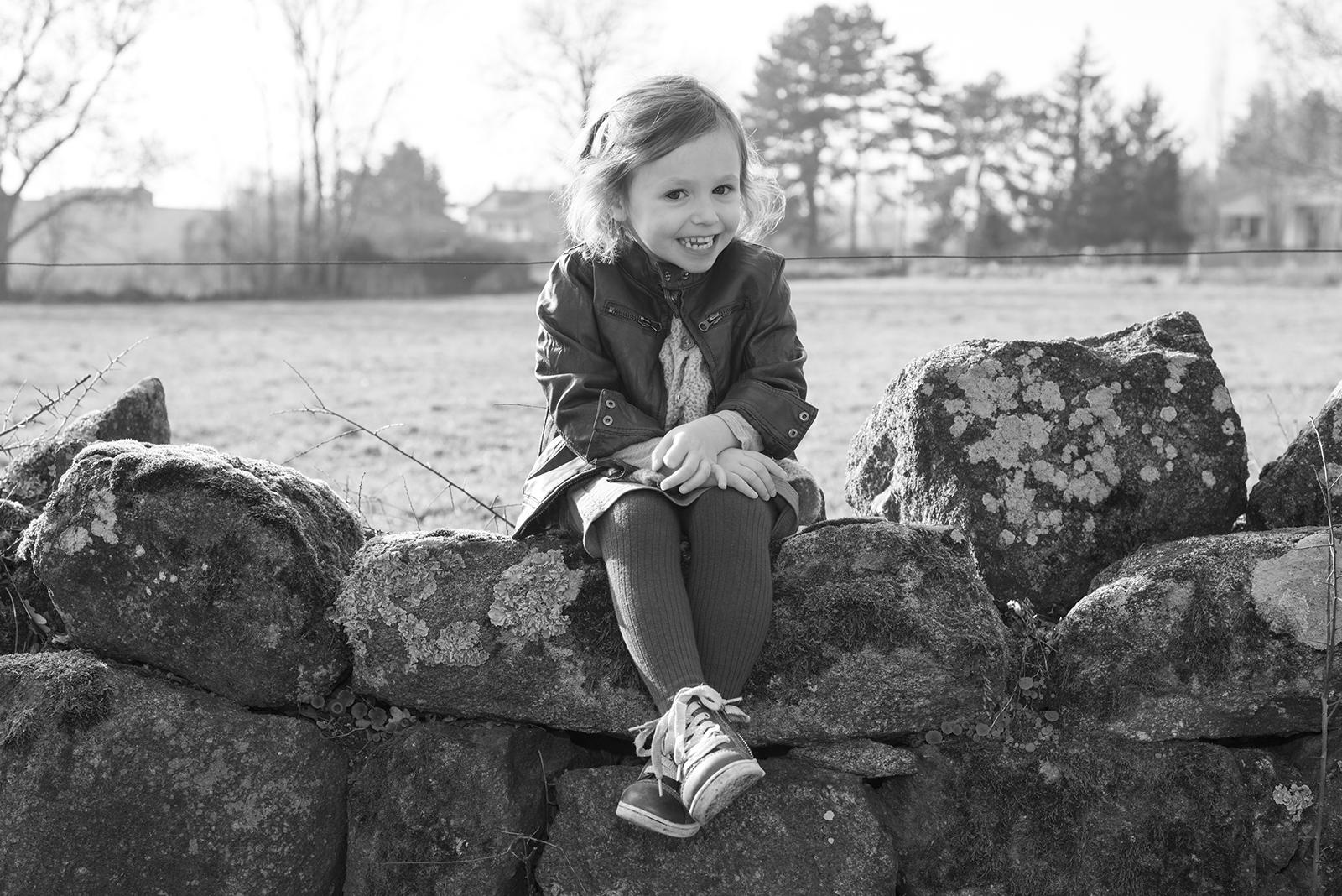 petite fille assise sur un muret