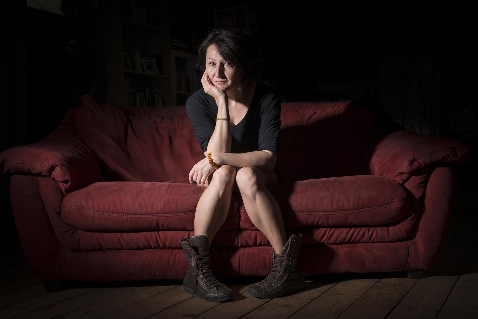 Jeune femme en robe noir asise sur un canapé rouge et lumière de cinéma