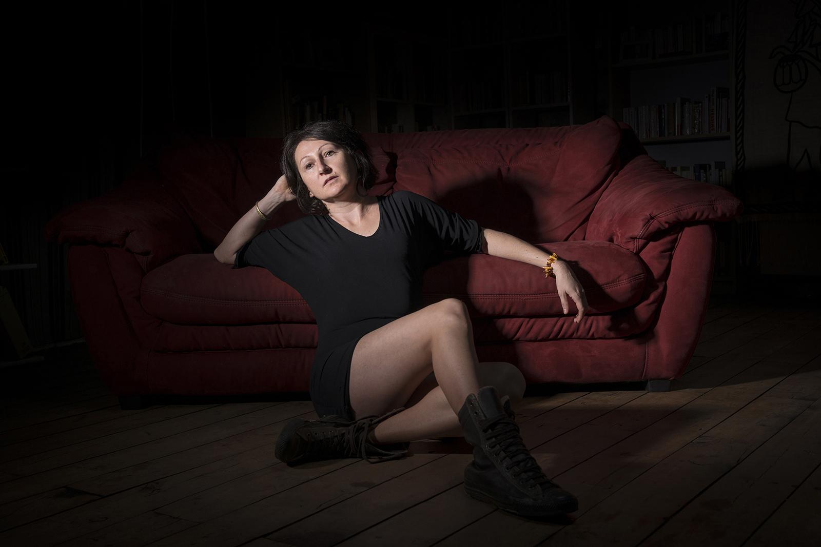 Jeaune femme assise par terre en studio au pied d'un canapé rouge