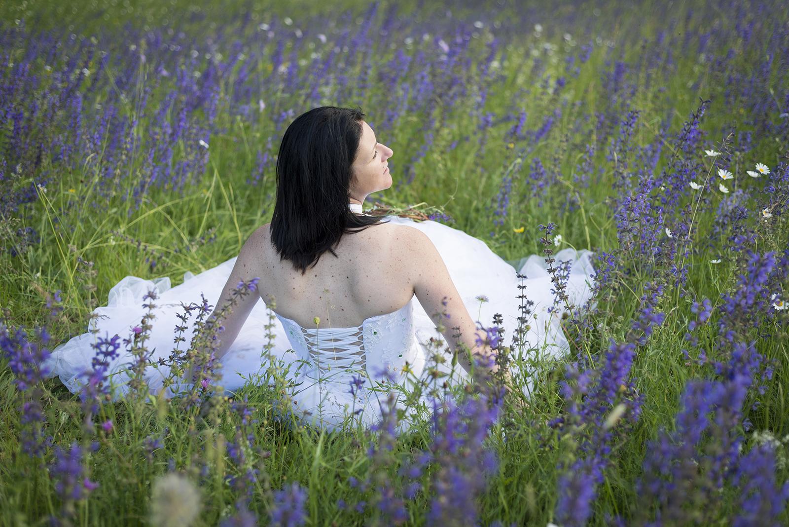 mariée de dos assise dans l'herbe