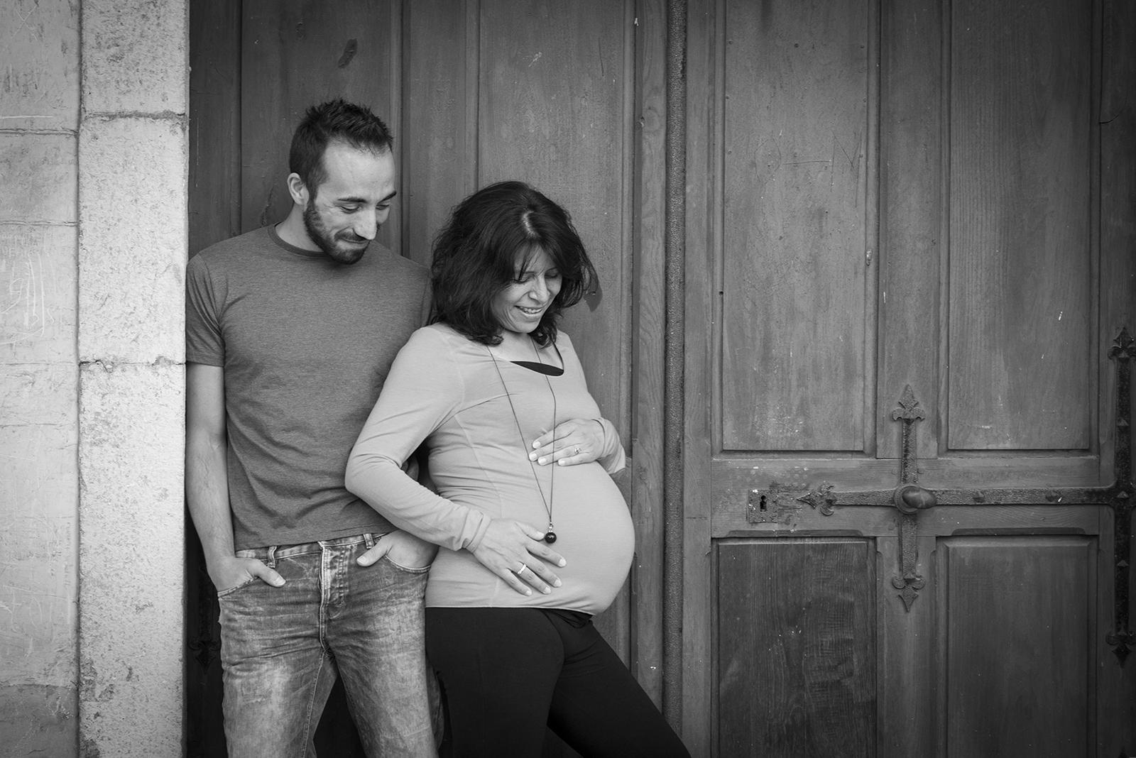 femme enceinte noir et blanc couple devant une vieille porte
