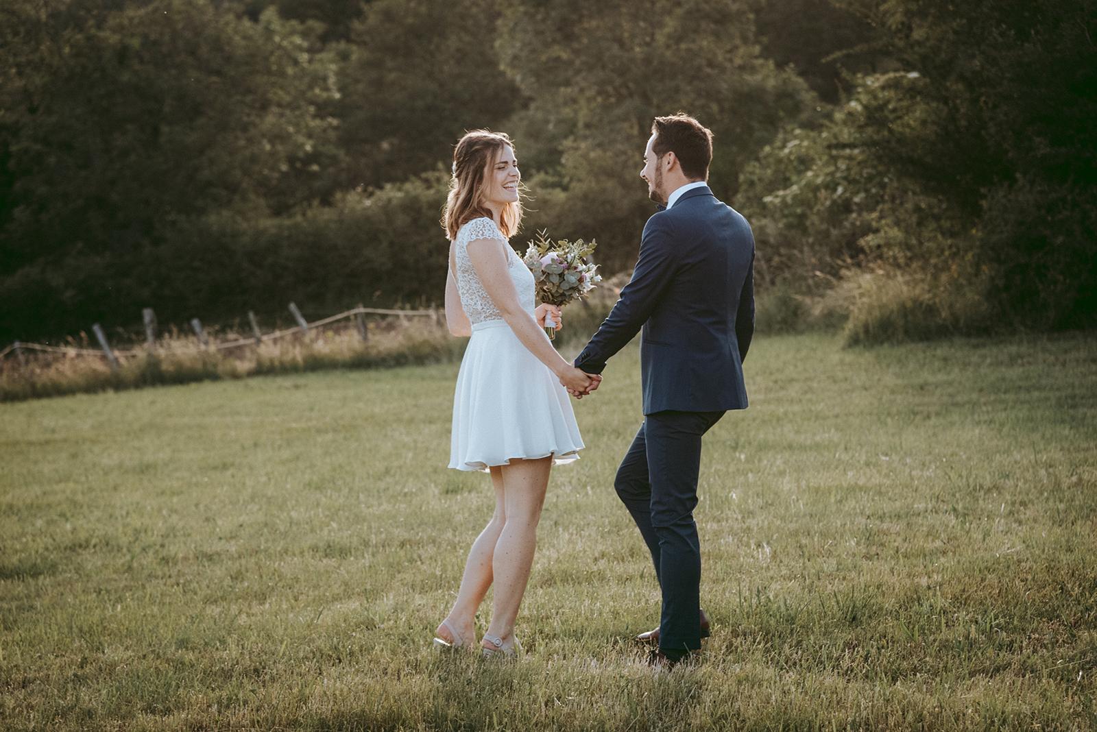 mariés dans un champs au coucher su soleil