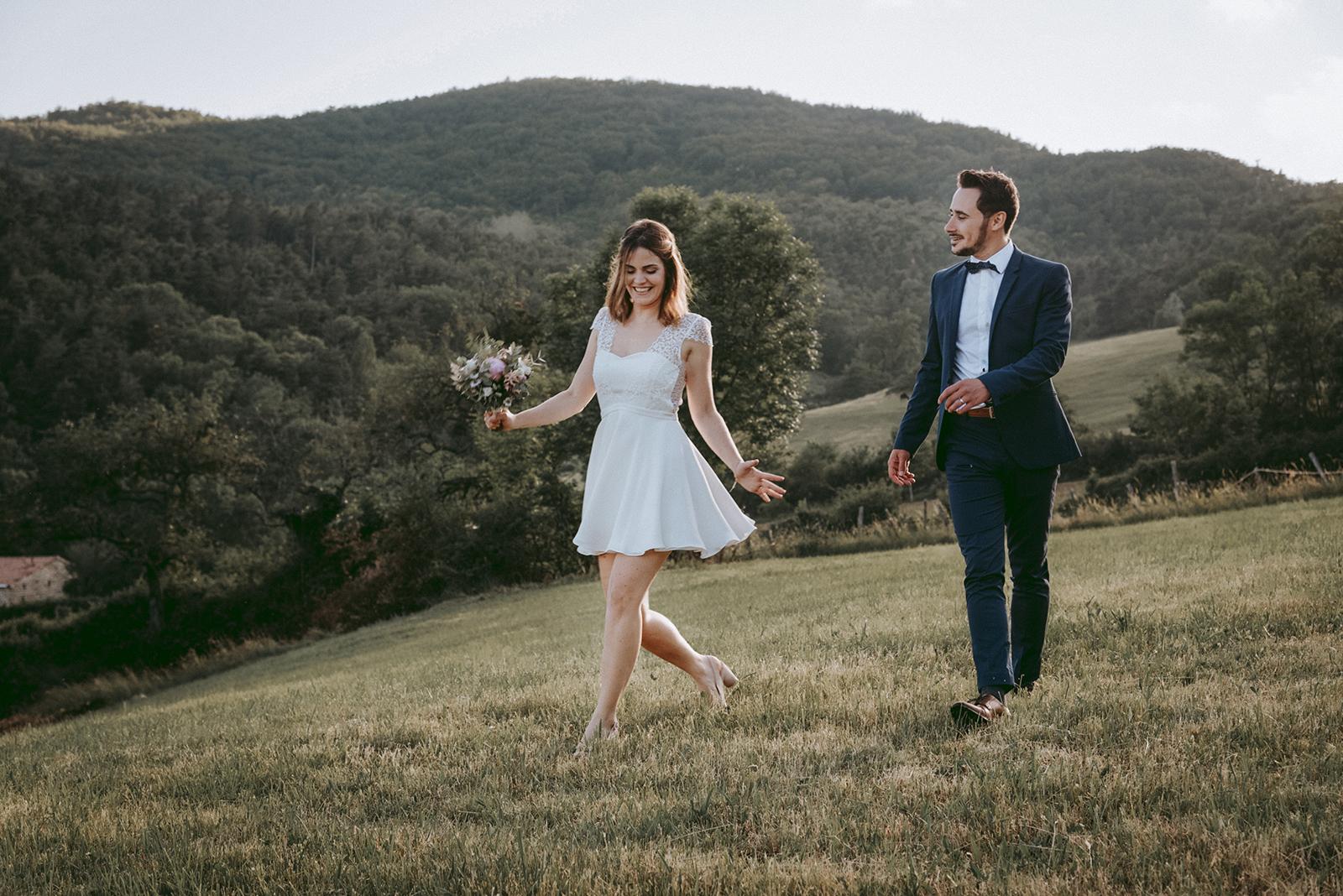 mariés qui marchent dans un champs au coucher du soleil