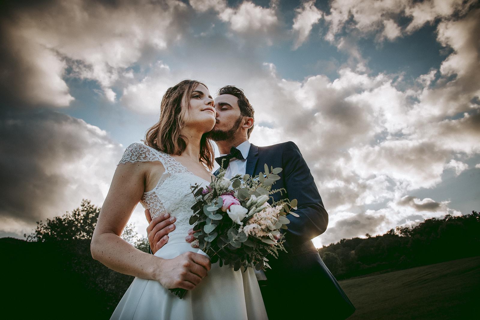 photo de couple de mariés avec ciel nuageux