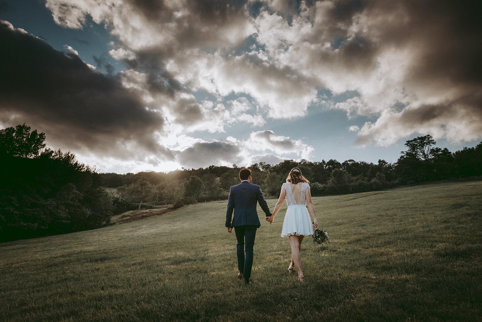 mariés qui marchent vers le ciel nuageux